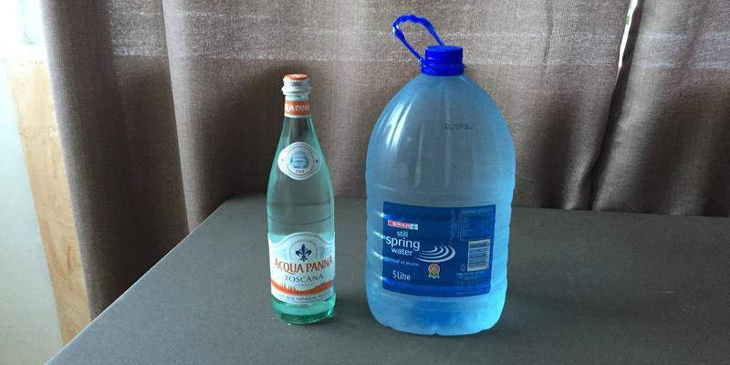 Plastikwasser und in der Glasflasche